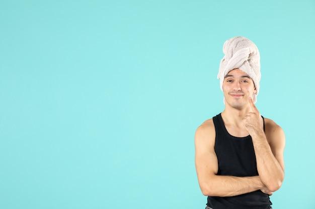 Vooraanzicht van jonge man na douche op blauwe muur