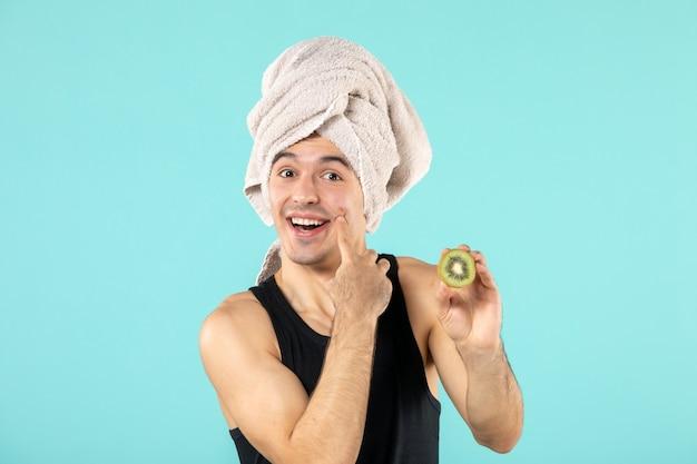 Vooraanzicht van jonge man na het douchen met plakjes kiwi op blauwe muur