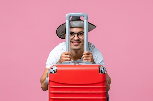 Vooraanzicht van jonge man poseren met zijn vakantietas op roze muur on