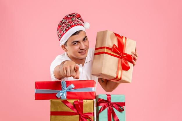 Vooraanzicht van jonge man rond verschillende kerstcadeautjes op de roze muur