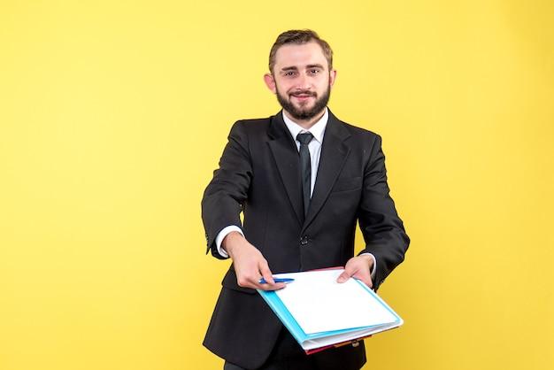 Vooraanzicht van jonge man zakenman met een glimlach wijst vol vertrouwen met een pen naar de documenten voor ondertekening op geel