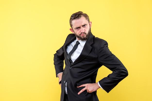 Vooraanzicht van jonge man zakenman schandalig hand in hand op de heupen op geel