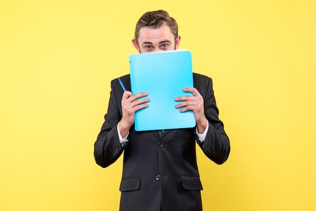 Vooraanzicht van jonge man zakenman verbergt het onderste deel van het gezicht met de blauwe map op geel