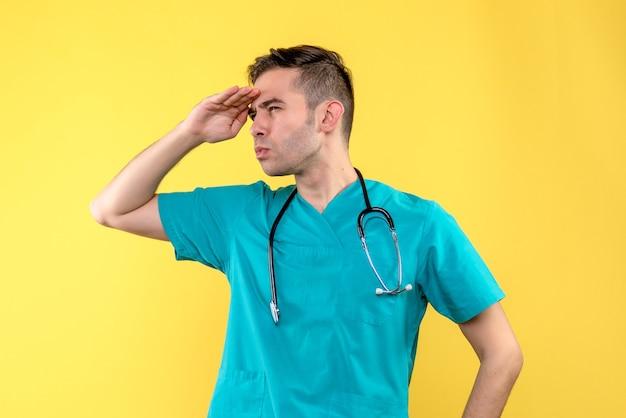 Vooraanzicht van jonge mannelijke arts die afstand op gele muur bekijkt