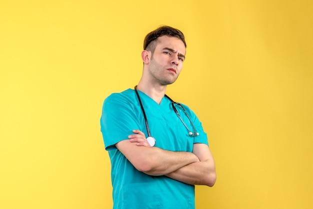 Vooraanzicht van jonge mannelijke arts die op gele muur denkt