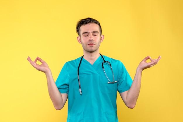 Vooraanzicht van jonge mannelijke arts die op gele muur mediteren