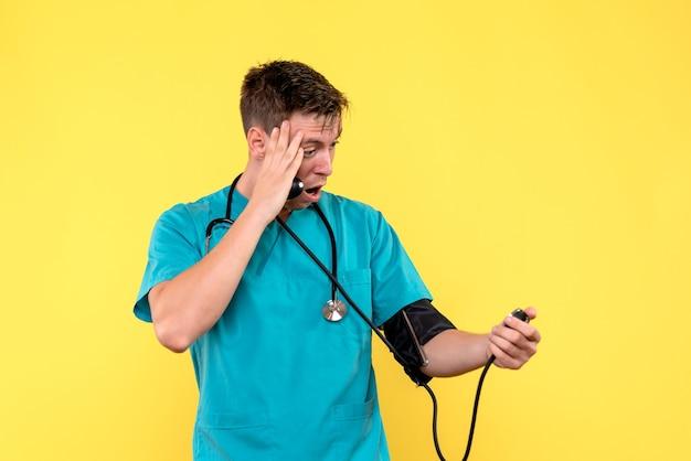 Vooraanzicht van jonge mannelijke arts die tonometer op gele muur gebruikt