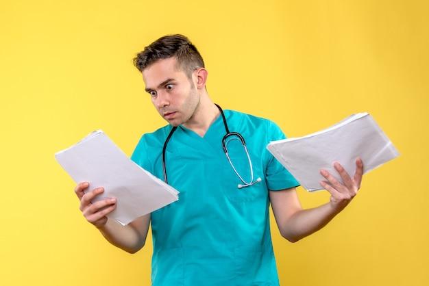 Vooraanzicht van jonge mannelijke arts met documenten op gele muur