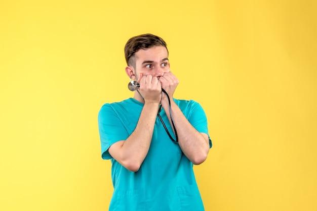 Vooraanzicht van jonge mannelijke arts met een stethoscoop op gele muur