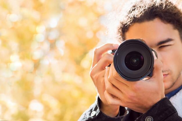 Vooraanzicht van jonge mannelijke fotograaf die foto's in de herfstbos neemt