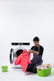 Vooraanzicht van jonge mannelijke kleren wassen met behulp van wasmachine op witte muur