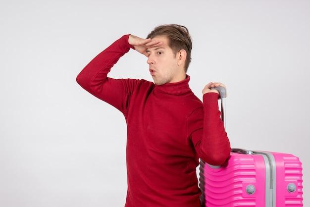 Vooraanzicht van jonge mannelijke roze draagtas op witte muur