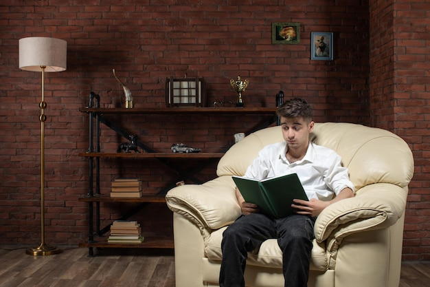 Vooraanzicht van jonge mannelijke zittend op de bank en het lezen van boek in kamer baan huis avondwerk