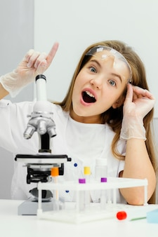 Vooraanzicht van jonge meisjeswetenschapper die microscoop met behulp van en een idee hebben