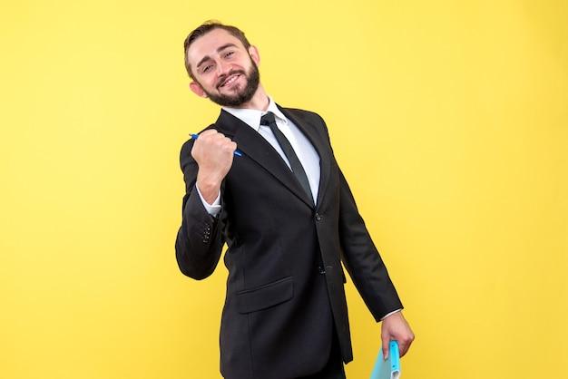 Vooraanzicht van jonge mensen tevreden zakenman die de pen gelukkig op geel houdt