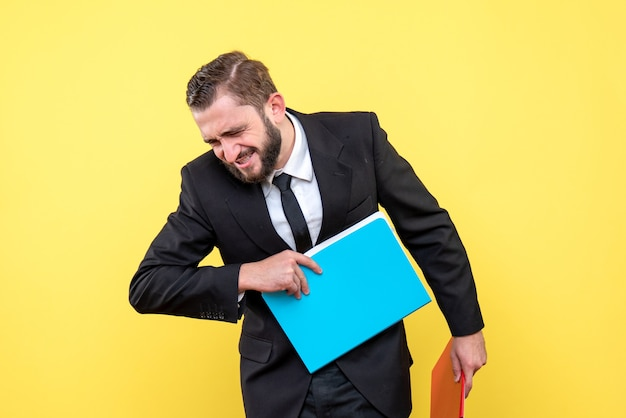 Vooraanzicht van jonge mensenzakenman die blauwe omslag op geel weggooit