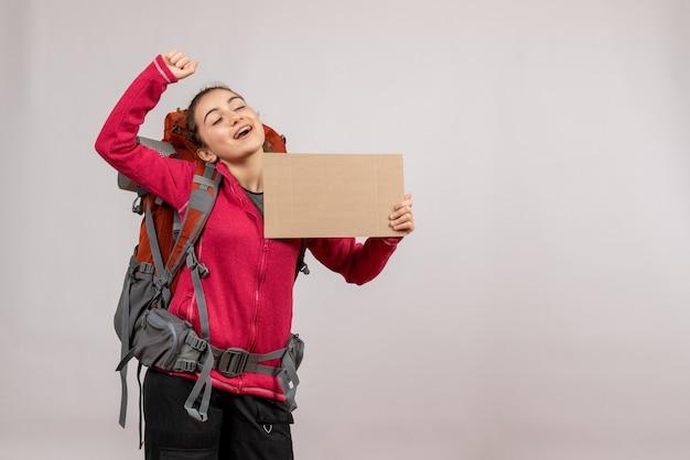 Vooraanzicht van jonge reiziger met grote rugzak die karton op grijze muur steunt