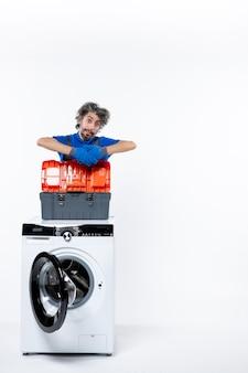 Vooraanzicht van jonge reparateur die zich achter wasmachine op wit geïsoleerde muur bevindt