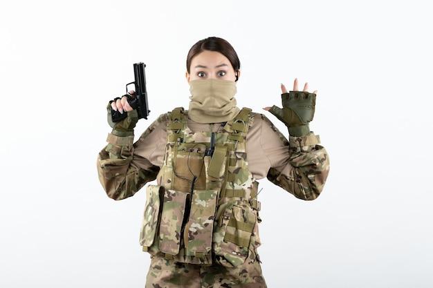 Vooraanzicht van jonge soldaat in camouflage die zich overgeeft met pistool op witte muur