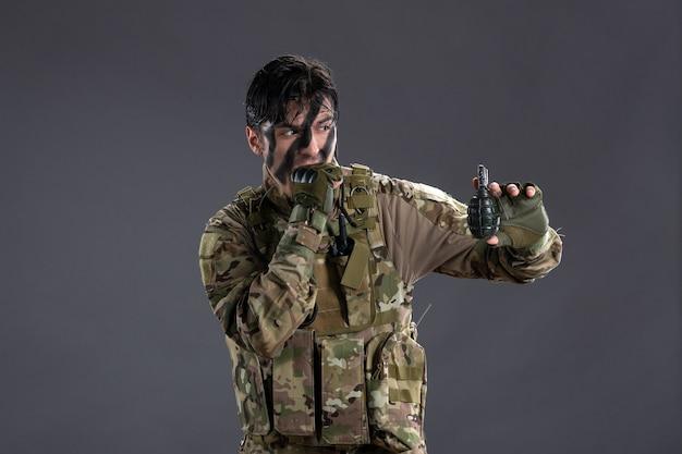 Vooraanzicht van jonge soldaat in camouflage met granaat op donkere muur