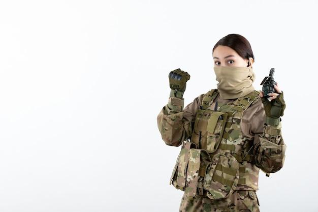 Vooraanzicht van jonge soldaat in camouflage met granaat witte muur
