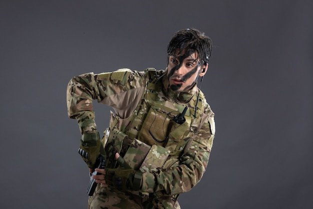 Vooraanzicht van jonge soldaat in camouflage met pistool op de donkere muur