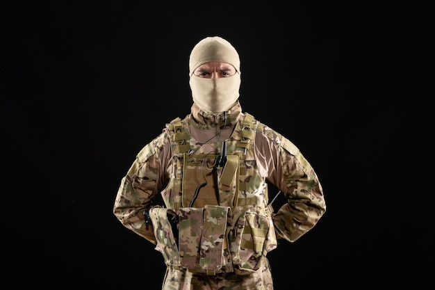 Vooraanzicht van jonge soldaat in uniform en masker op zwarte muur