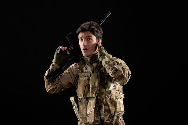 Vooraanzicht van jonge soldaat in uniform met geweer op zwarte muur