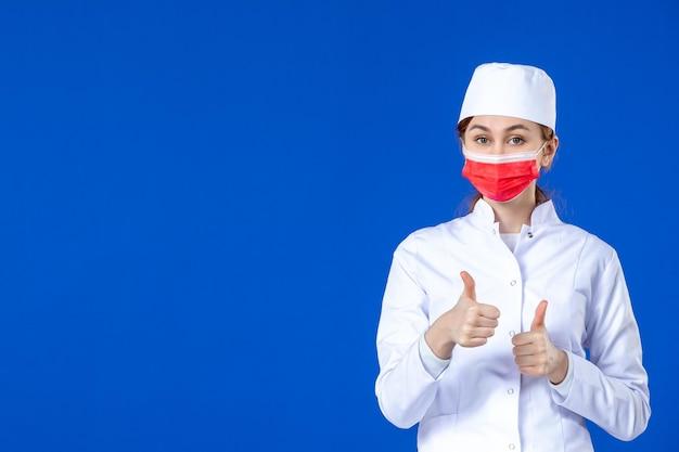 Vooraanzicht van jonge verpleegster in medisch kostuum met rood masker op blauw