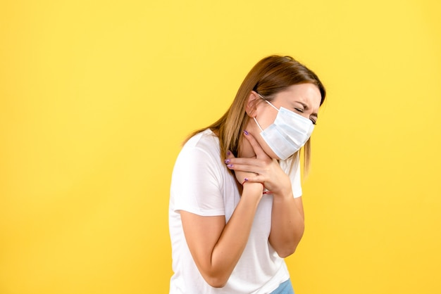 Vooraanzicht van jonge vrouw die ademhalingsproblemen op gele muur heeft