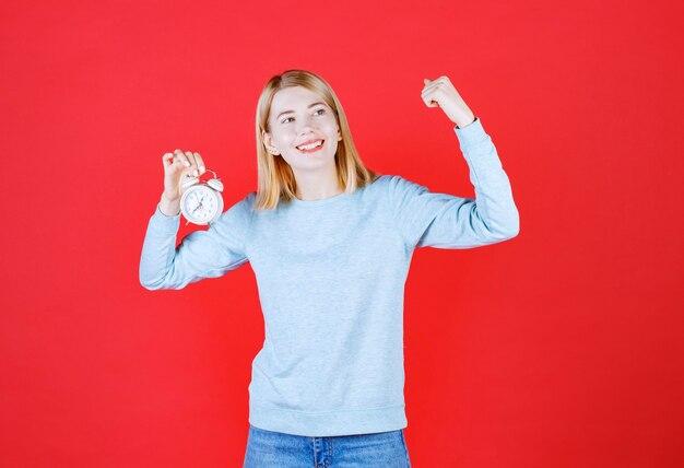 Vooraanzicht van jonge vrouw die een klok houdt en haar wapen opheft om spier op rood te tonen