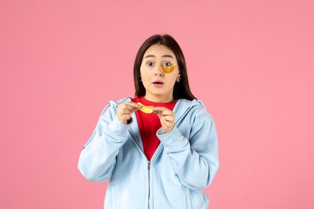 Vooraanzicht van jonge vrouw die een masker maakt voor haar gezicht op roze muur