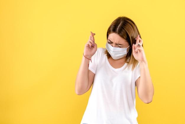 Vooraanzicht van jonge vrouw die haar vingers op gele muur kruist