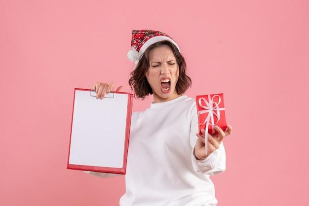Vooraanzicht van jonge vrouw die kleine aanwezige kerstmis houdt en nota over de roze muur indient