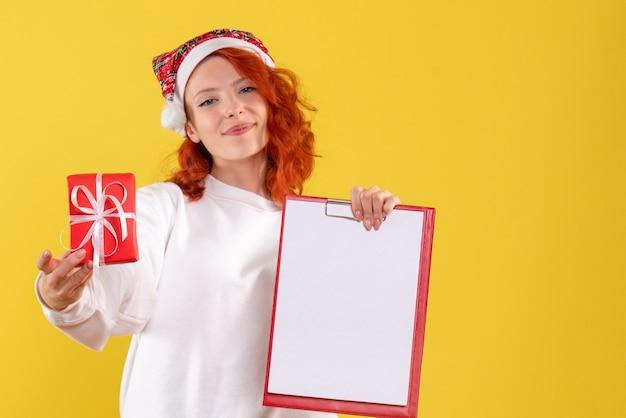 Vooraanzicht van jonge vrouw die kleine aanwezige kerstmis houdt en nota over gele muur indient