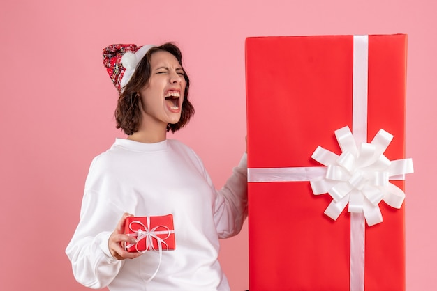 Vooraanzicht van jonge vrouw die kleine kerstmis met grote op de roze muur aanwezig houdt