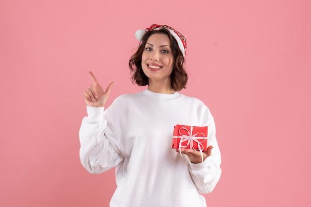 Vooraanzicht van jonge vrouw die kleine kerstmis op roze muur houdt