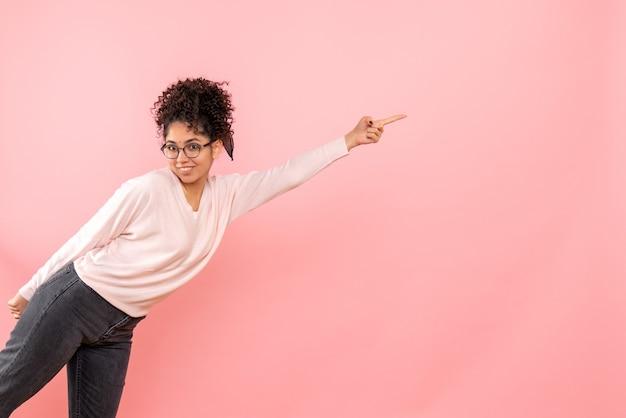 Vooraanzicht van jonge vrouw die op de roze muur glimlacht