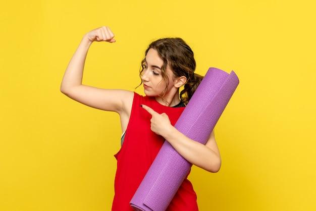 Vooraanzicht van jonge vrouw die paars tapijt houdt en op gele muur buigt