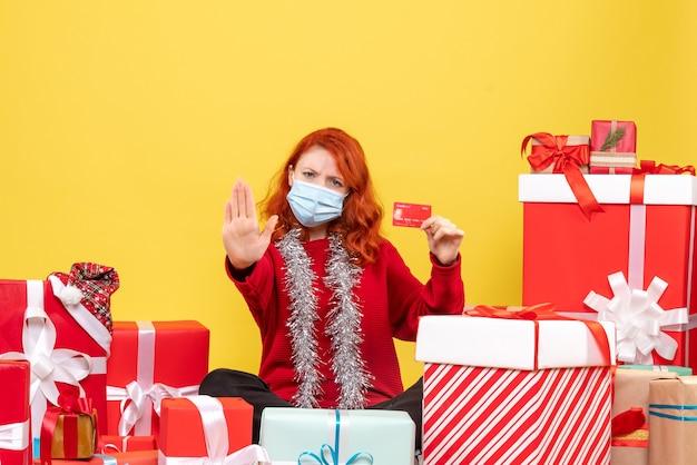 Vooraanzicht van jonge vrouw die rondhangen stelt in masker met bankkaart op gele muur voor