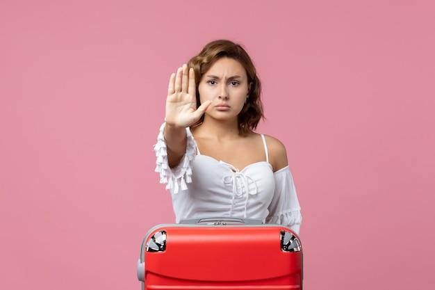 Vooraanzicht van jonge vrouw die stopbord met rode vakantietas op roze muur toont