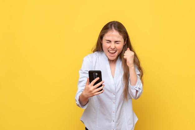 Vooraanzicht van jonge vrouw die telefoon vasthoudt en zich verheugt