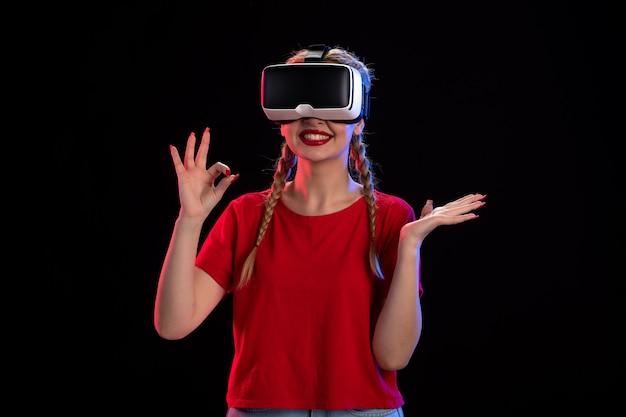 Vooraanzicht van jonge vrouw die virtual reality speelt op donkere echografie