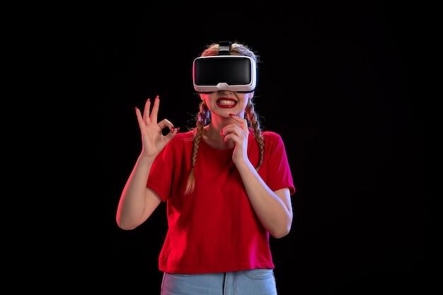 Vooraanzicht van jonge vrouw die virtual reality speelt op donkere muur