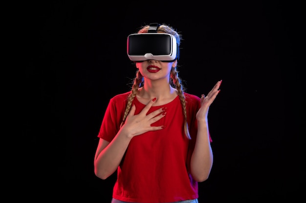 Vooraanzicht van jonge vrouw die virtual reality speelt op donkere visual