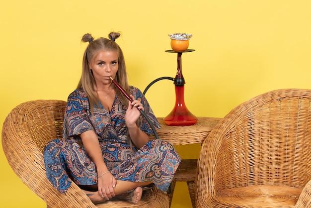 Vooraanzicht van jonge vrouw die waterpijp rookt op lichtgele muur