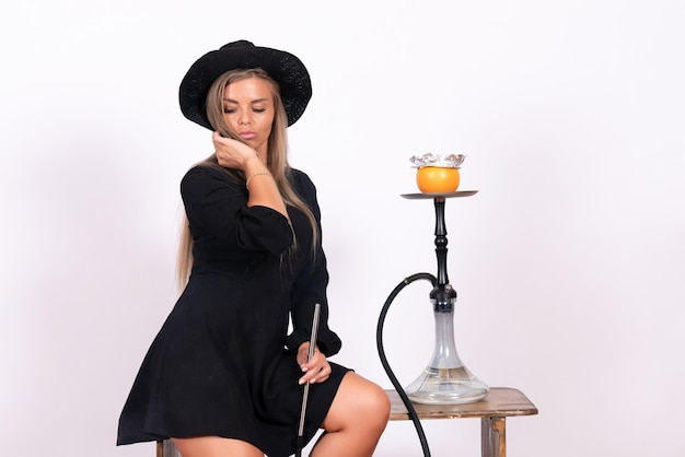 Vooraanzicht van jonge vrouw die waterpijp rookt op witte muur white