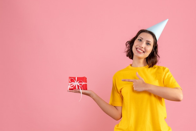 Vooraanzicht van jonge vrouw die weinig aanwezig op roze muur houdt