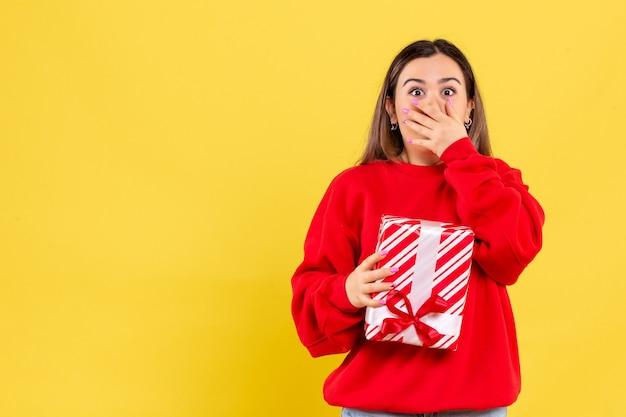 Vooraanzicht van jonge vrouw die weinig gift houdt die op gele muur wordt geschokt
