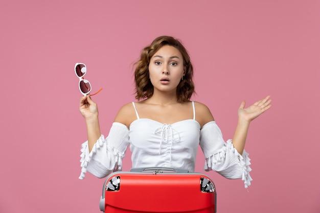 Vooraanzicht van jonge vrouw die zich voorbereidt op een reis met rode tas op de roze muur